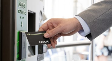 Man tapping a PRESTO card on a PRESTO device