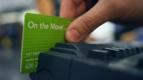 Hand swiping green On the Move membership card through magnetic stripe reader keyboard
